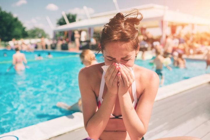 Kobieta w stroju kąpielowym, siedzi nad basenem z chusteczką przy nosie