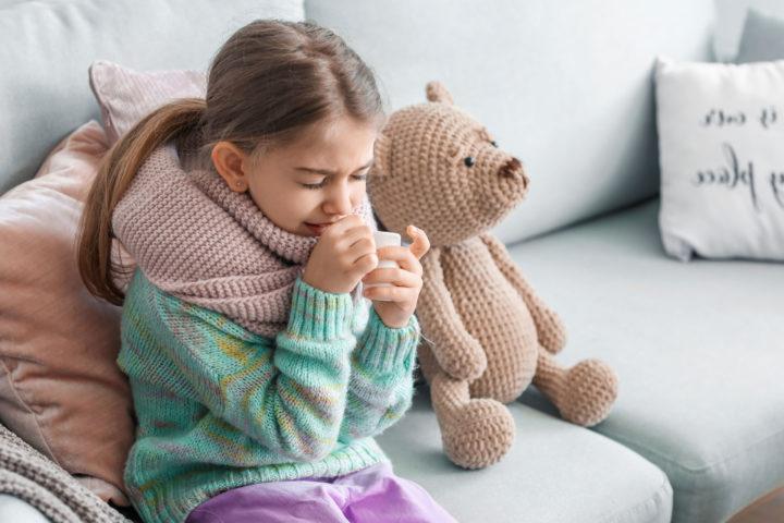 Chora dziewczynka owinięta szalikiem kaszle