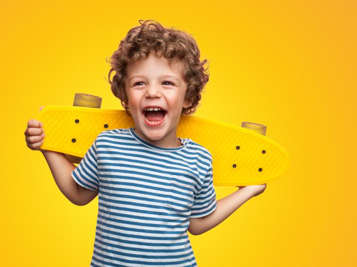 Uśmiechnięty chłopczyk z deskorolką